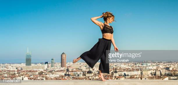 young blond modern dancer dancing in the streets of lyon, france with a panorama of the city in background - dancing photos et images de collection