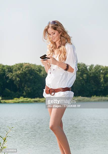 Young blond woman at lake with smartphone