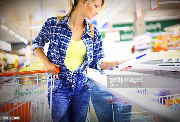 Young blond woman buying food in local supermarket.