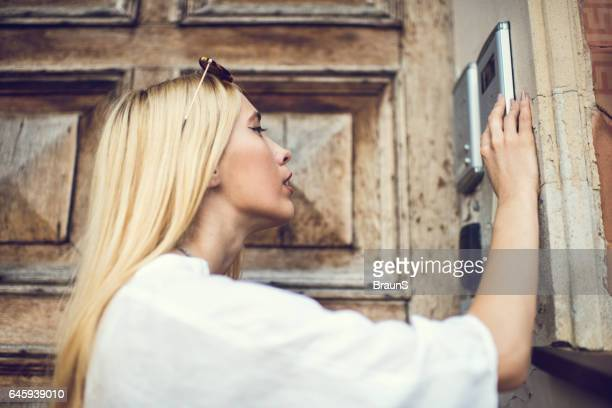 young blond woman dialing password on intercom. - intercom stock photos and pictures