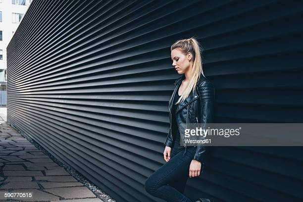 Young blond woman dressed in black leaning against black facade