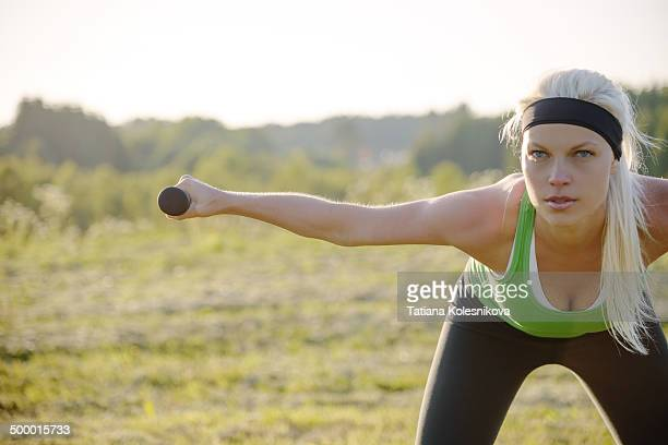 young blond woman exercising with dumbbells - blonde forte poitrine photos et images de collection