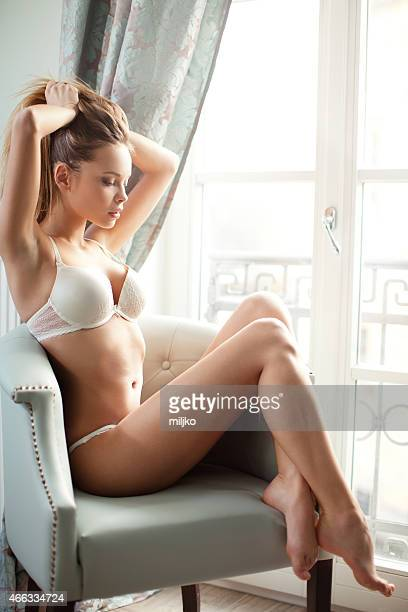 Young blond woman in underwear sitting next to the window