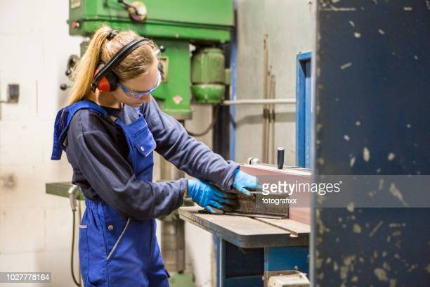 young blond woman is deburring a piece steal at a surface grinder in a workshop - ear protection stock pictures, royalty-free photos & images