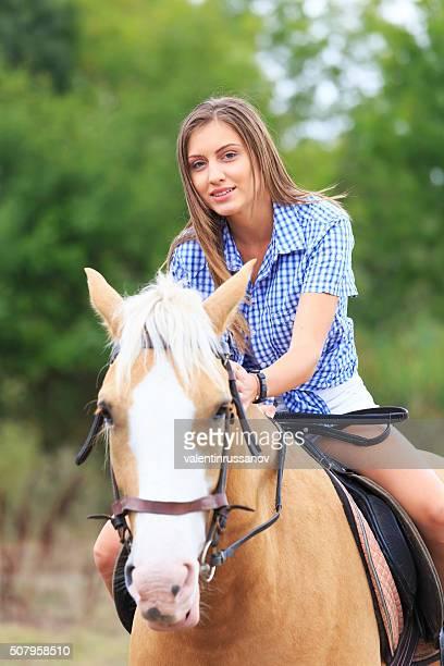 Junge Blonde Frau auf dem Pferd