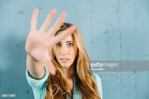 Young blond woman raising her hand