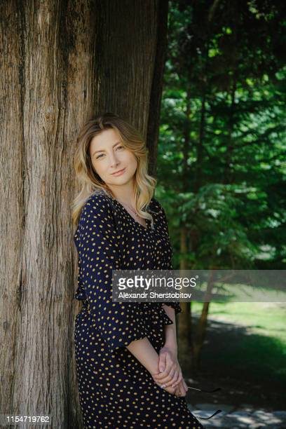 Young blond woman relaxing at old tree
