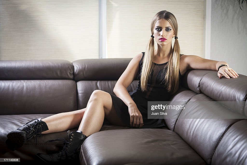 young blond woman sitting on leather sofa in house picture id171140308