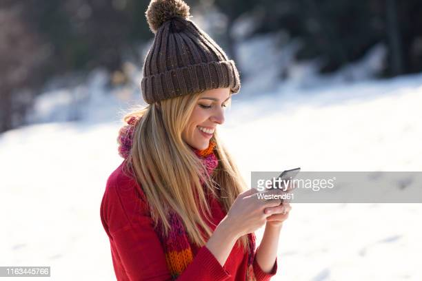 young blond woman using smartphone in winter - brown hat stock pictures, royalty-free photos & images