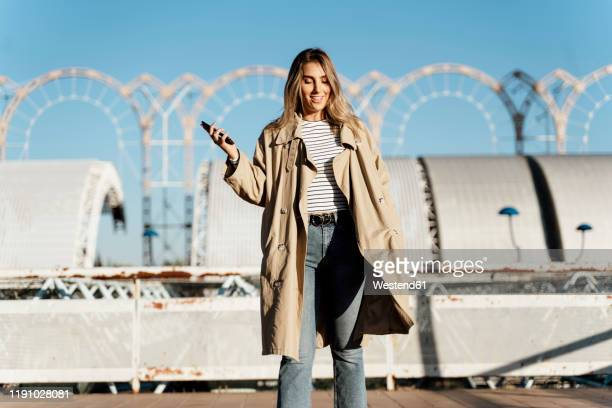 young blond woman using smartphone - trench coat stock pictures, royalty-free photos & images