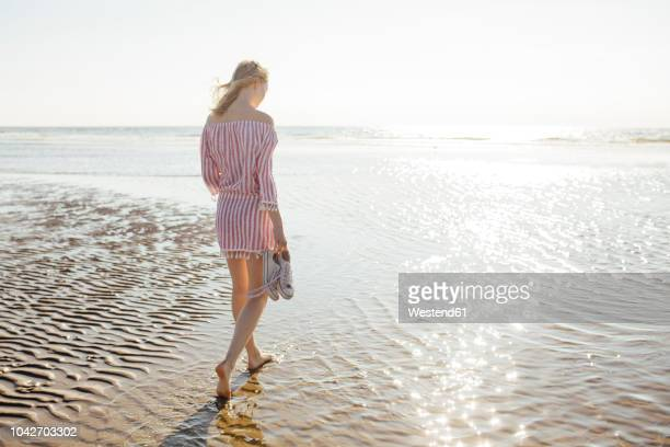 young blond woman walking at the beach - barfuß stock-fotos und bilder