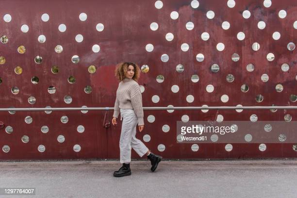 young blond woman walking by maroon metallic wall - looking over shoulder stock pictures, royalty-free photos & images