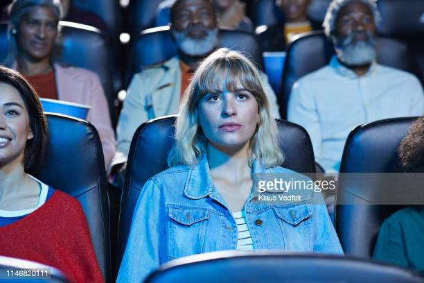 young blond woman watching movie with smiling friend in theater - film industry stock pictures, royalty-free photos & images