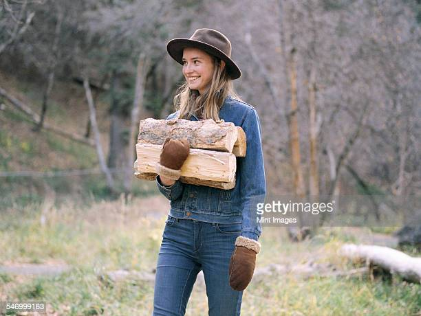 Young blond woman wearing a hat, carrying firewood.