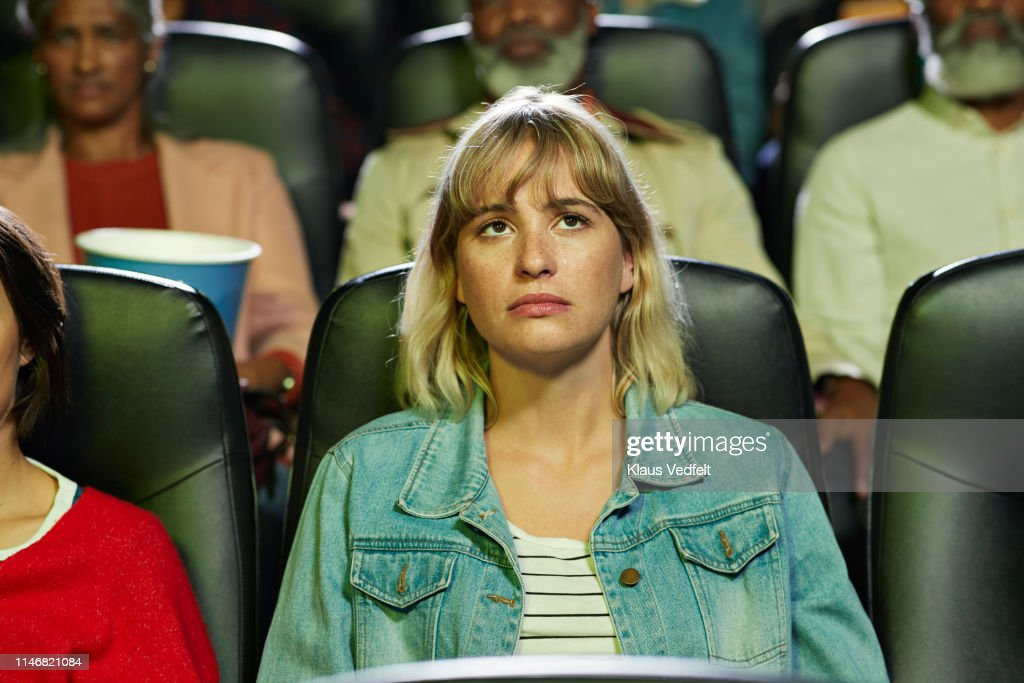 Young blond woman with blank expression watching movie in theater : Stock Photo