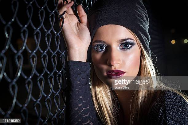 Young blond woman with hat against fence at night