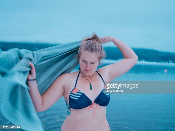 young, blond women drys off with towel after 2020 new years polar bear swim in shuswap lake - 25 29 years stock pictures, royalty-free photos & images