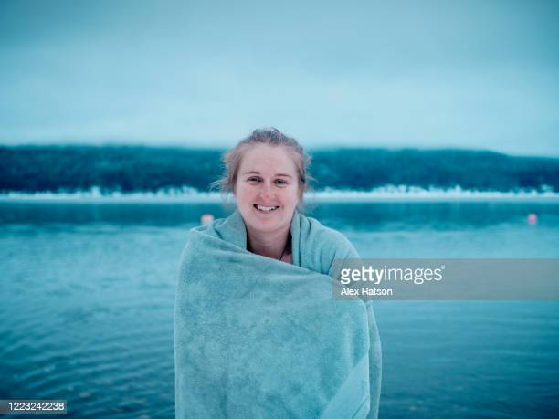 young, blond women warms up with towel after 2020 new years polar bear swim in shuswap lake - 25 29 years stock pictures, royalty-free photos & images