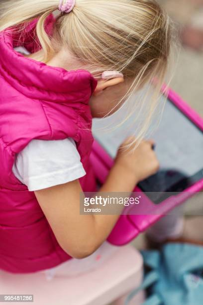 young blonde deaf girl wearing a hearing aid using a tablet device - assistive technology stock photos and pictures