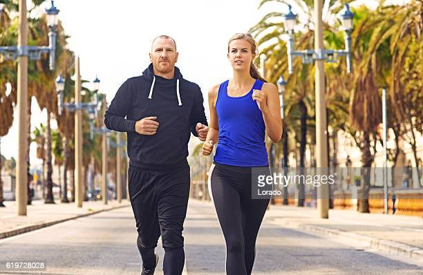 Young blonde female and personal trainer jogging in warm surroundings