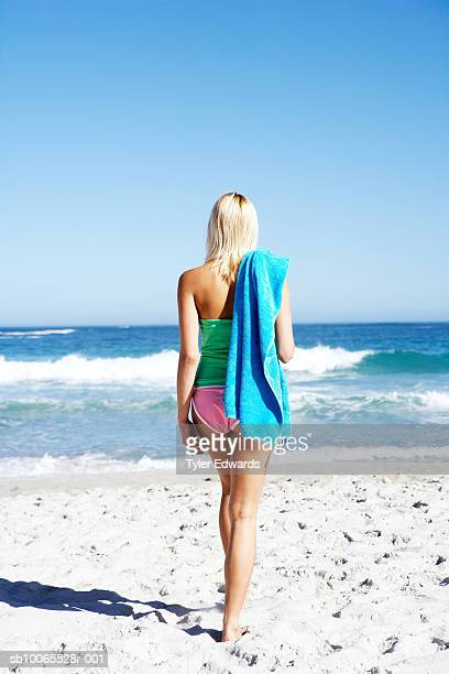 Young blonde female carrying towel over shoulder walking towards ocean, rear view