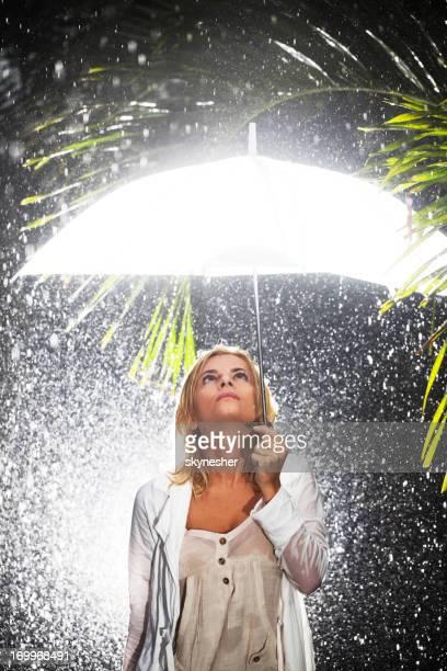 Junge blonde Frau hält einen Regenschirm und Blick nach oben.
