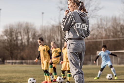 Young Blonde Female Soccer Coach and her Girl Football team 923184844