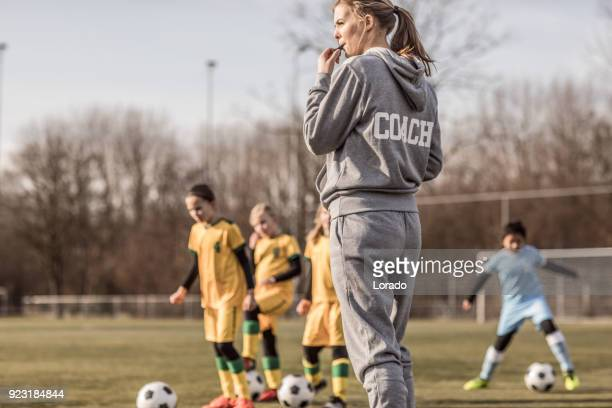 young blonde female soccer coach and her girl football team - coach stock pictures, royalty-free photos & images
