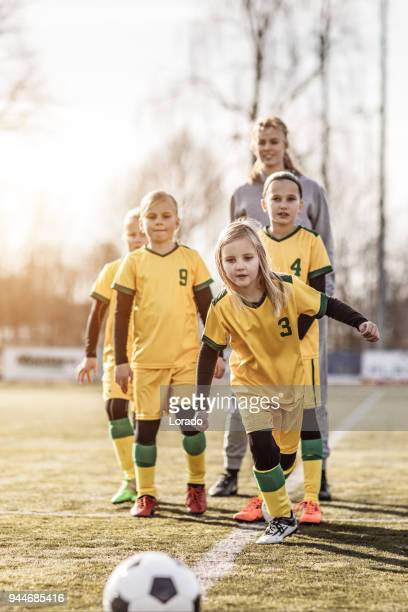 young blonde female soccer coach and her girl football team - club football stock pictures, royalty-free photos & images