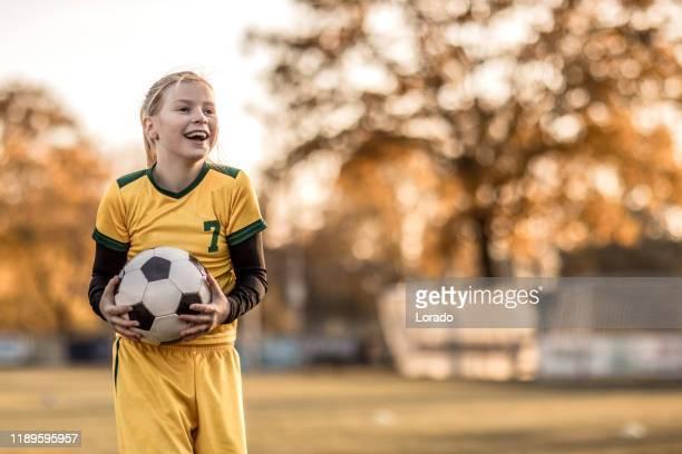 jonge blonde vrouwelijke voetbal meisje tijdens voetbalopleiding - sporting term stockfoto's en -beelden