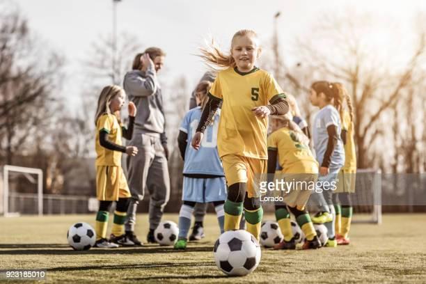 jeune blonde femme fille football posant pour une photo de joueur pendant l'entraînement de football - capitaine d'équipe photos et images de collection