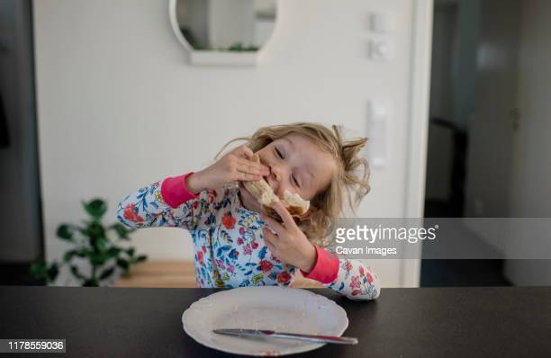 young blonde girl eating her food and making faces at home - sanduíche imagens e fotografias de stock