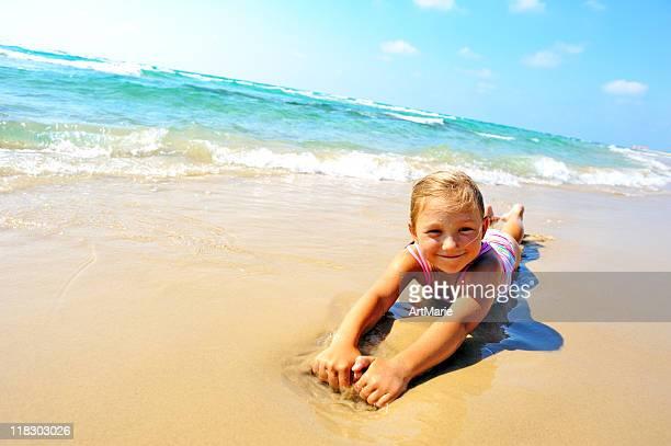 Joven rubia Chica cavando en la playa de arena