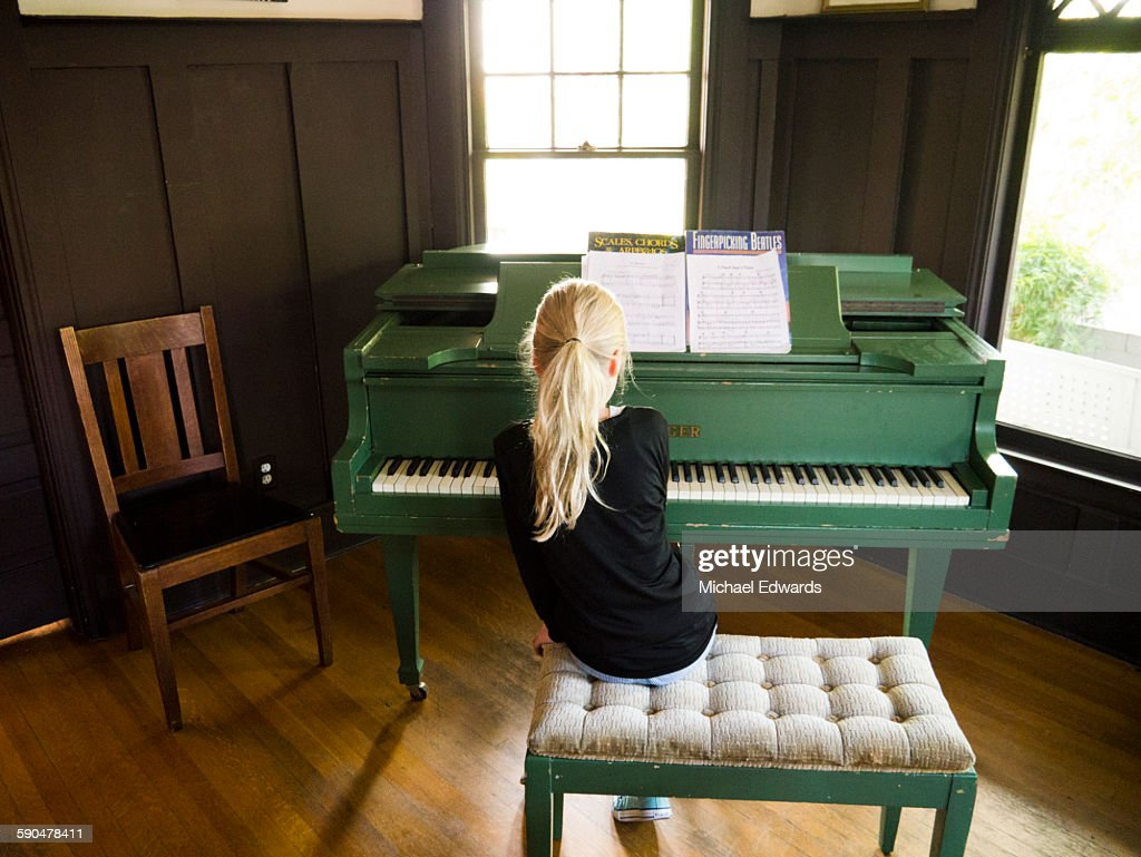 young blonde girl playing piano : Stock Photo