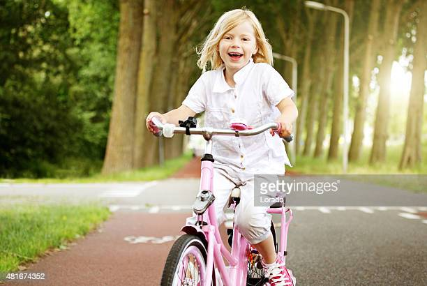 Young blonde girl riding her bike