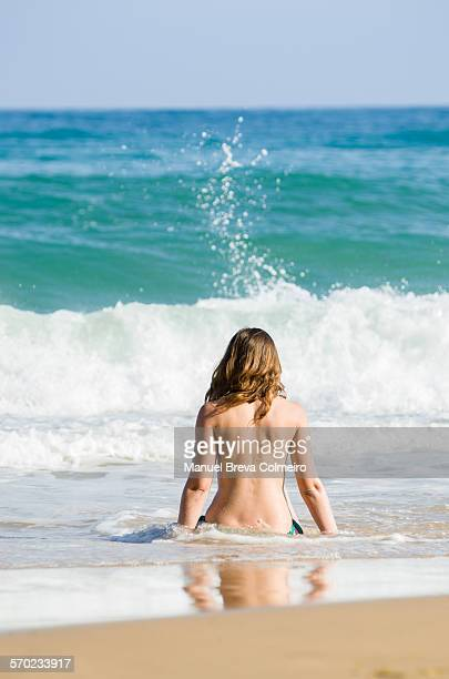 Young blonde girl topless on the beach