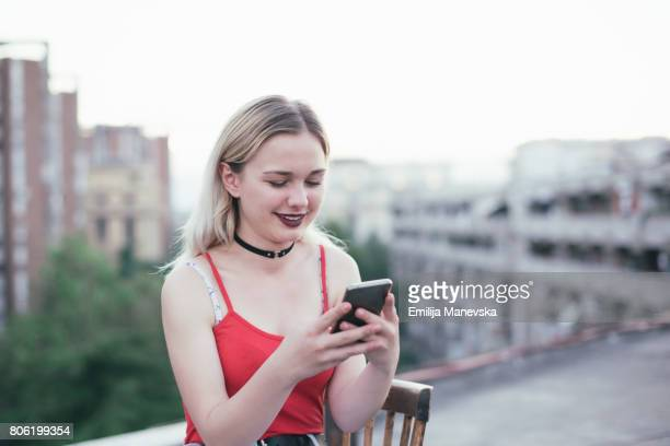 Young blonde girl using smartphone