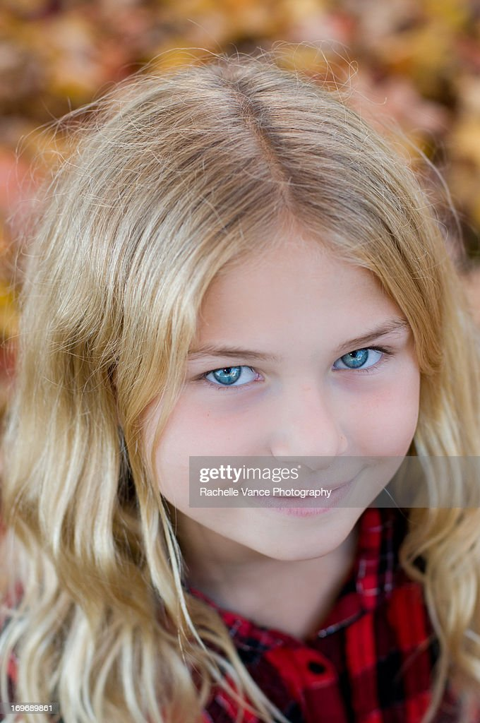 Young Blonde Girl With Blue Eyes Around Fall Leave Stock