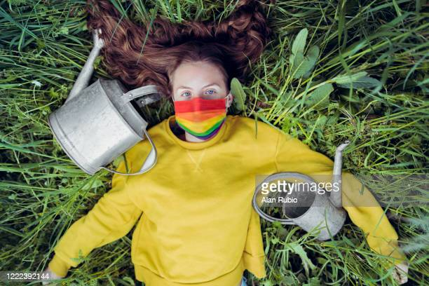 young blonde girl with blue eyes, in a green meadow surrounded by watering cans with a mask with the flag of gay pride - lgbtq stock pictures, royalty-free photos & images
