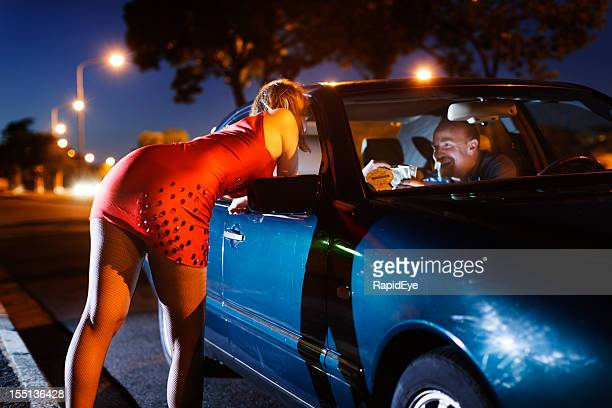 young blonde prostitute soliciting man in car - hoeren stockfoto's en -beelden