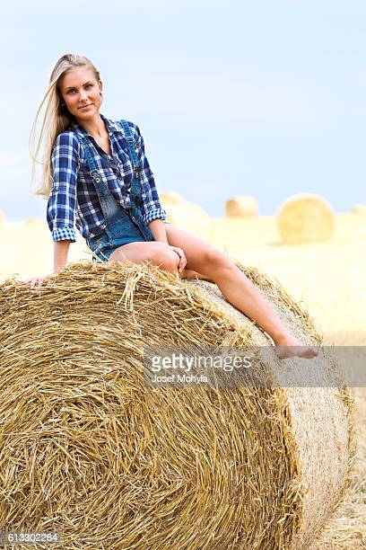 Young blonde sitting on bale of straw on field