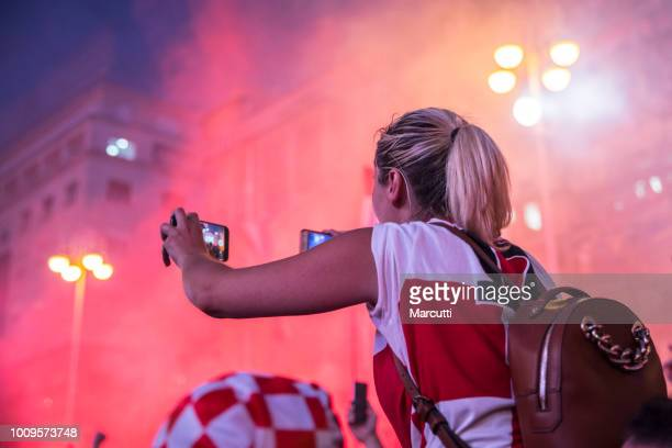 Young blonde taking photo on welcome celebration Croatian soccer team