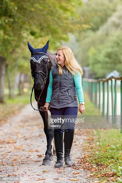 若いブロンドの女性があり、黒い馬の家 - funny black girl ストックフォトと画像