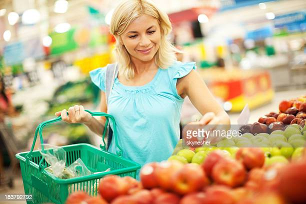 Young Blonde woman buys apples in a supermarket.