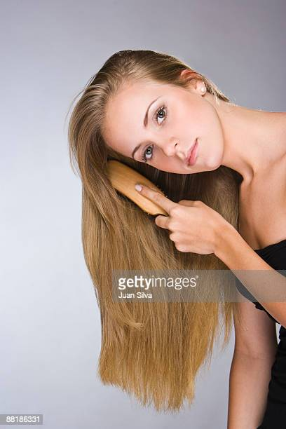 Young blonde woman combing her hair, portrait