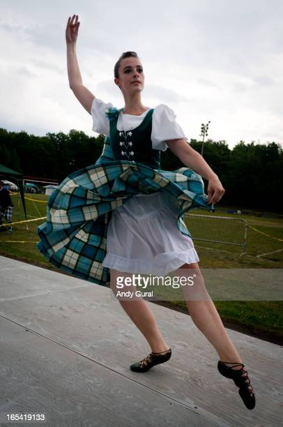 Young blonde woman dances in highland dress on an outdoor stage in a sports field. The sky is grey overcast and her skirts are flying as she is in...