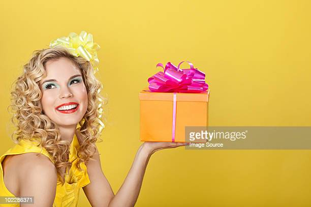 Young blonde woman holding birthday present against yellow background