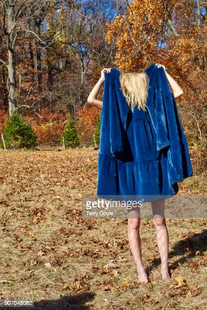 Young blonde woman in a blue overcoat, outside during autumn