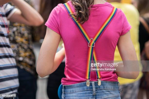 young blonde woman in a crowd wearing colorful rainbow suspenders. - istock photos et images de collection