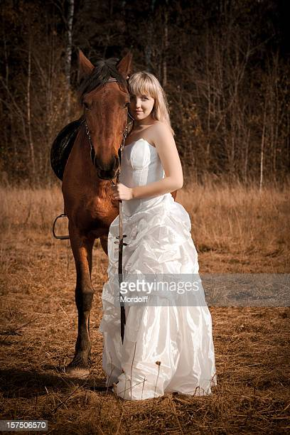 Young blonde woman in white dress standing with horse